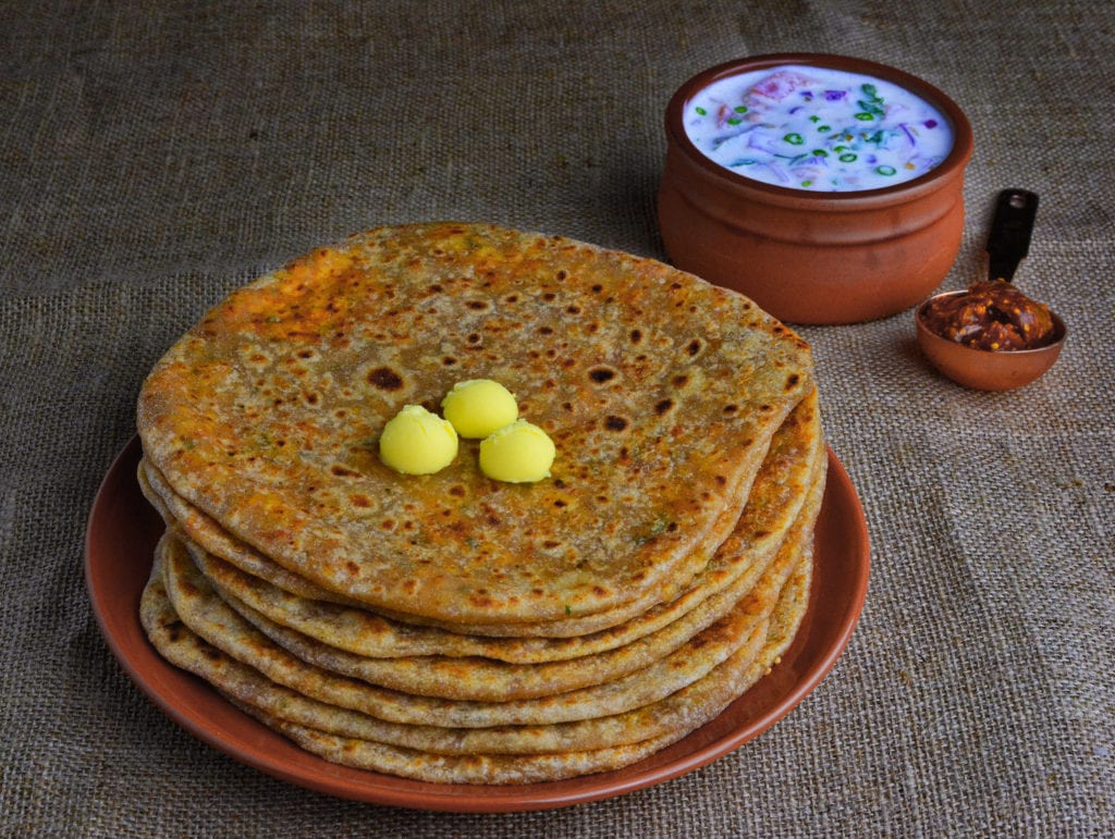 Paneer paratha served with raita and pickle